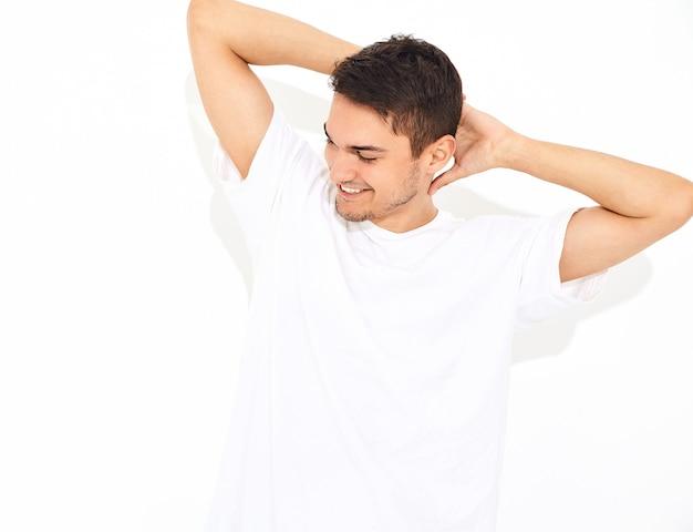 Portret van de knappe glimlachende jonge modelmens gekleed in jeanskleren en t-shirt het stellen. zijn hoofd aanraken Gratis Foto