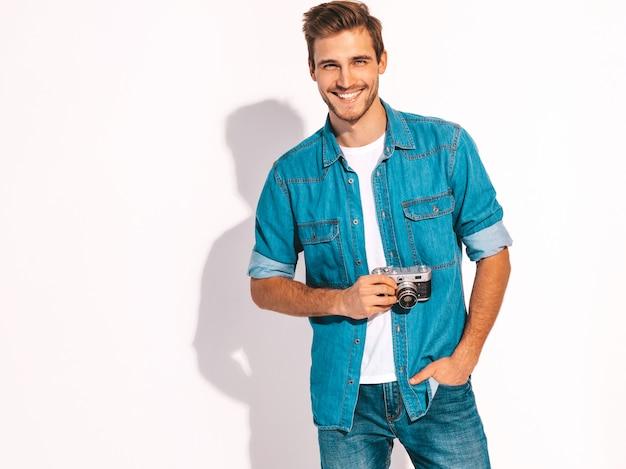 Portret van de knappe glimlachende mens die de kleren van de zomerjeans draagt. model man met vintage fotocamera. Gratis Foto