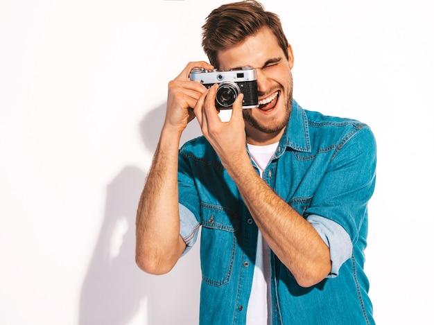 Portret van de knappe glimlachende mens die de kleren van de zomerjeans draagt. model mannetje dat beeld op oude uitstekende fotocamera neemt. Gratis Foto