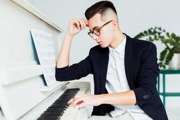 Portret van de knappe jonge mens die de piano speelt Gratis Foto