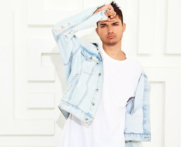 Portret van de knappe jonge modelmens gekleed in jeanskleren die dichtbij witte geweven muur stellen Gratis Foto