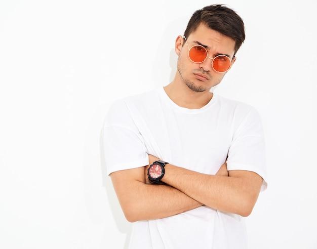 Portret van de knappe jonge modelmens gekleed in jeanskleren en t-shirt in zonnebril het stellen. gekruiste armen Gratis Foto