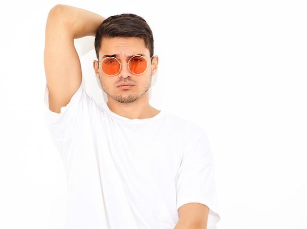 Portret van de knappe jonge modelmens gekleed in jeanskleren en t-shirt in zonnebril het stellen. zijn hoofd aanraken Gratis Foto