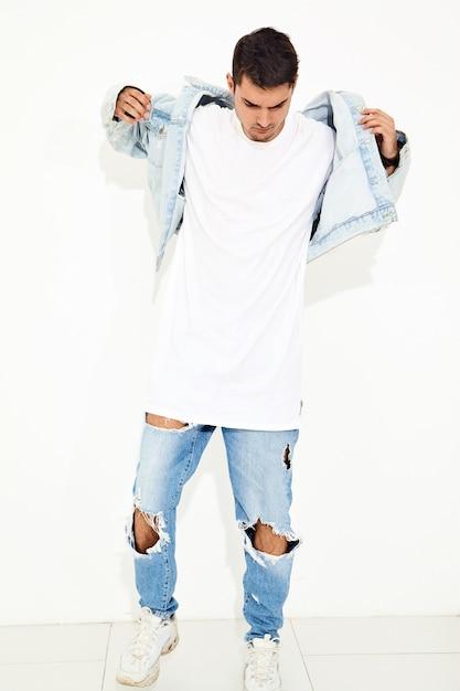 Portret van de knappe jonge modelmens gekleed in jeanskleren het stellen. geïsoleerd Gratis Foto