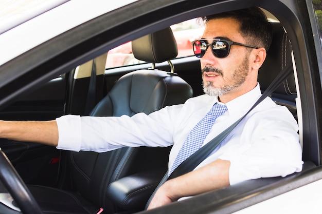 Portret van de knappe mens die de auto drijft Gratis Foto