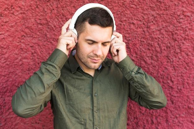 Portret van de man met hoofdtelefoon luisteren muziek Gratis Foto