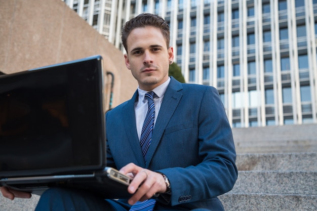 Portret van de mens in elegant kostuum die aan treden met laptop op knieën werken. Premium Foto