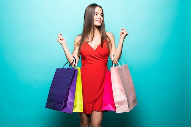 Portret van de mooie jonge vrouw met boodschappentassen op de blauwe muur Gratis Foto
