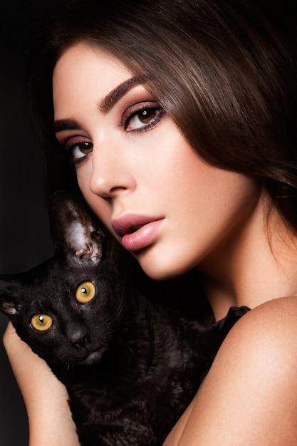 Portret van de mooie jonge vrouw met kat Premium Foto