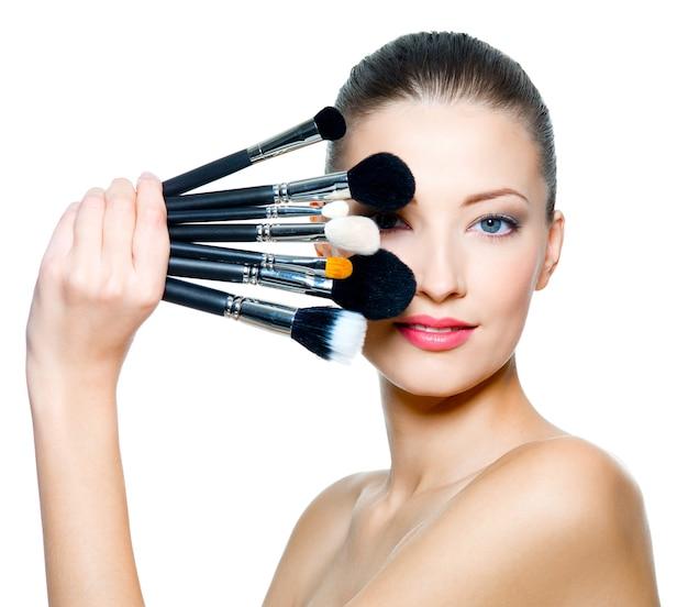 Portret van de mooie vrouw met make-upborstels dichtbij aantrekkelijk gezicht. Gratis Foto
