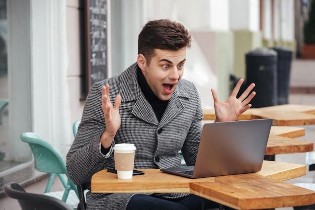 Portret van de verraste opgewonden mens die emotioneel in zilveren laptop kijkt, gilt en zich verheugt Gratis Foto