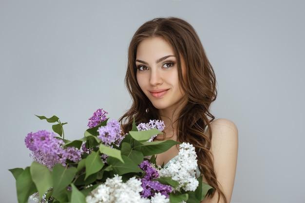 Portret van de vrouw met een boeket lentebloemen Premium Foto