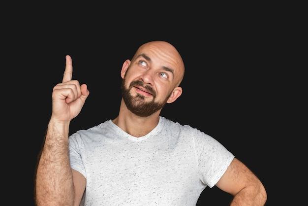 Portret van de witte kale mens met baard in witte t-shirt die en duim glimlacht toont Premium Foto