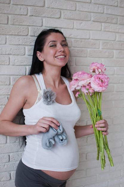 Portret van de zwangere vrouw met bloemen Premium Foto