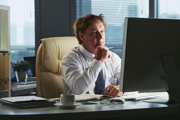 Portret van directeur bezig met lezen financieel rapport Gratis Foto