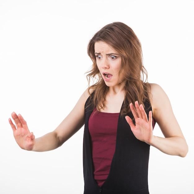 Portret van doen schrikken vrouw die handen omhoog ter verdediging opheffen Gratis Foto