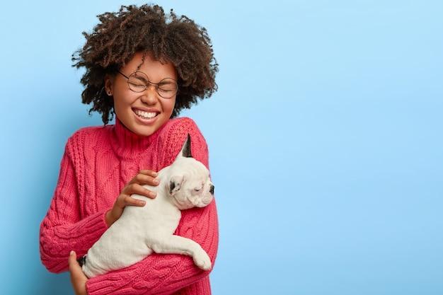 Portret van dolblij vrouwelijke hondeneigenaar houdt kleine witte pup, lacht positief, in goed humeur na buitenwandeling met favoriete huisdier, gekleed in casaul trui, heeft afro haar. dieren concept Gratis Foto