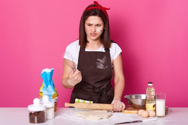 Portret van donkerharige meisje in schort bevuild met bloem, t-shirt en rode haarband, staat met garde in handen en voelt walgt van bak taarten, wil rust hebben. baker maakt heerlijke koekjes. Gratis Foto