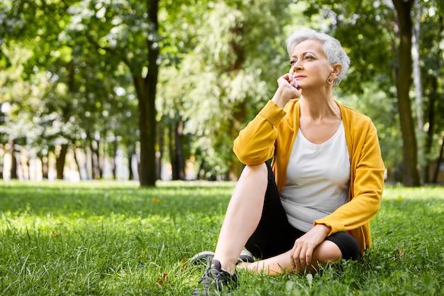 Portret van doordachte gepensioneerde vrouw in hardloopschoenen comfortabel zittend op groen gras, hand onder haar kin, kijken naar mensen lopen in park met peinzende gezichtsuitdrukking, ontspannen gevoel Gratis Foto