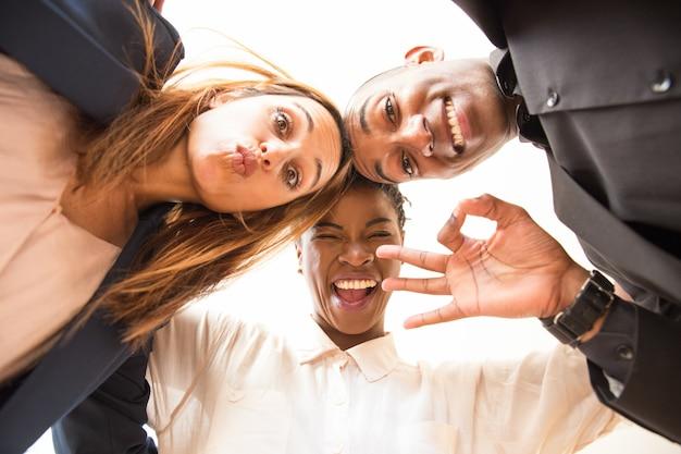 Portret van drie gelukkige collega's omarmen en grimassen Gratis Foto
