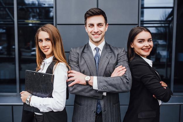 Portret van drie jonge glimlachende advocaten die gekruiste wapens bevinden zich. Premium Foto