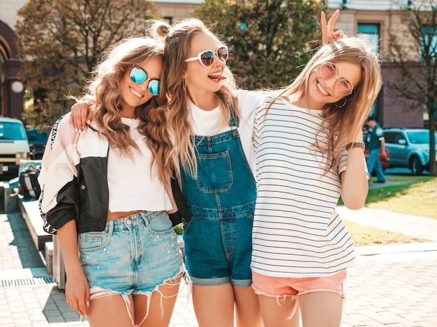 Portret van drie jonge mooie glimlachende hipster meisjes in trendy zomerkleren. sexy zorgeloze vrouwen die zich voordeed op straat. positieve modellen met plezier in een zonnebril Gratis Foto