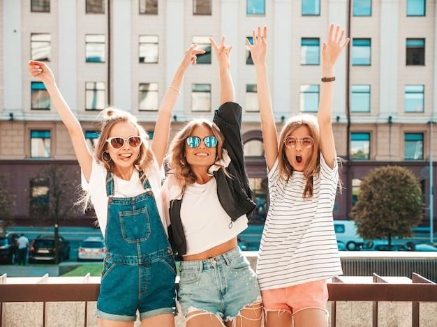 Portret van drie jonge mooie glimlachende hipster meisjes in trendy zomerkleren. sexy zorgeloze vrouwen die zich voordeed op straat. positieve modellen met plezier Gratis Foto