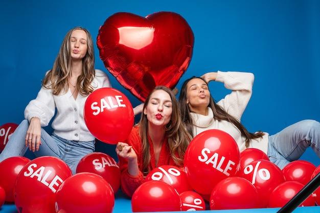 Portret van drie vrij lachende vriendinnen in casual kleding zitten met rode lucht ballonnen met verkoop- en procentteken Premium Foto