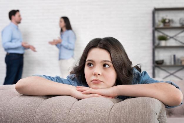 Portret van droevig meisje met ouders die erachter debatteren Gratis Foto