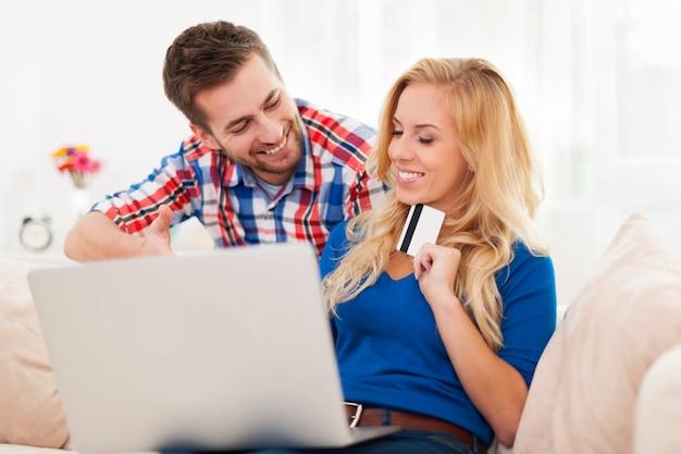 Portret van echtpaar met laptop en creditcard in de woonkamer Gratis Foto