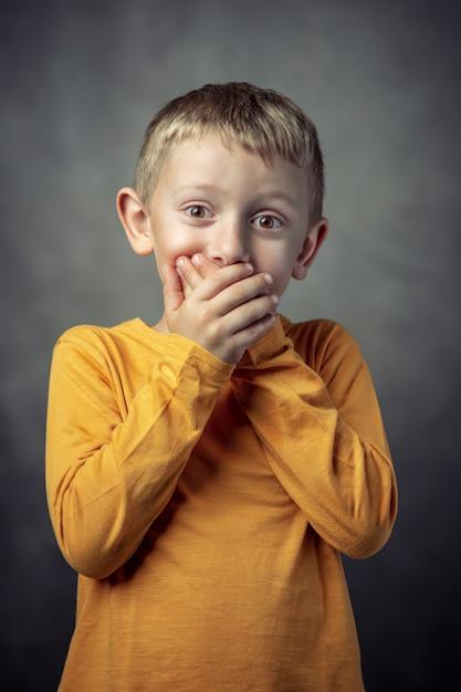 Portret van een 6-jarige jongen die zijn mond bedekt met beide handen. Premium Foto