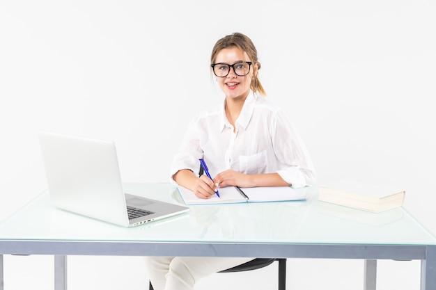 Portret van een aanbiddelijke bedrijfsvrouw die bij haar bureau met laptop en administratie werkt die op witte achtergrond wordt geïsoleerd Gratis Foto