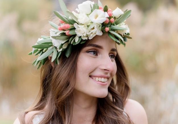 Portret van een aantrekkelijke brunette vrouw in een krans gemaakt van eustomas met een mooie glimlach Gratis Foto