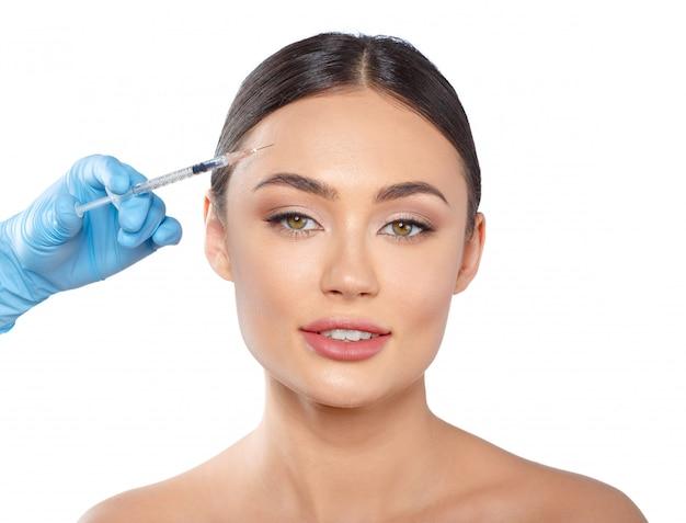 Portret van een aantrekkelijke jonge vrouw die botoxbehandeling ontvangt. Premium Foto