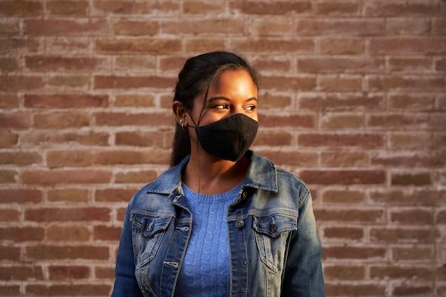 Portret van een afrikaanse amerikaanse zwarte die gezichtsmasker in openlucht draagt. Premium Foto