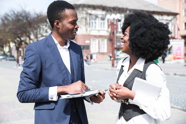 Portret van een afrikaanse jonge zakenman en onderneemster die aan elkaar in de stad spreken Gratis Foto
