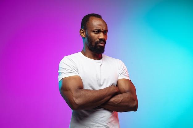 Portret van een afro-amerikaanse jongeman op gradiëntstudio in neon Gratis Foto