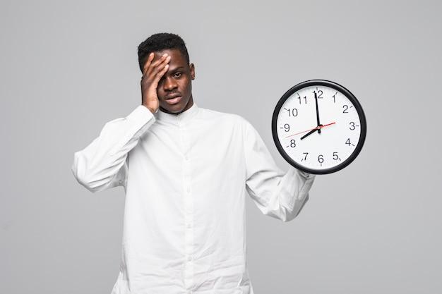 Portret van een afro-amerikaanse man met muur slaperige klok 7 uur in de ochtend geïsoleerd op een witte achtergrond Gratis Foto