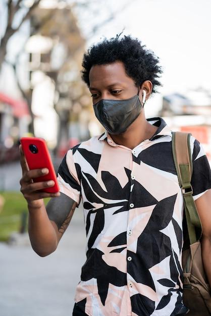 Portret van een afro-toeristische man met zijn mobiele telefoon tijdens het wandelen buiten op straat Gratis Foto
