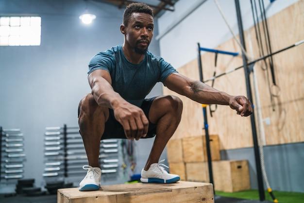 Portret van een atletische man die bokssprongoefening doet. crossfit, sport en gezonde levensstijl. Gratis Foto
