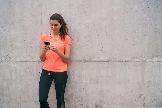 Portret van een atletische vrouw met behulp van haar mobiele telefoon tijdens een pauze van de training. sport en gezondheid levensstijl. Gratis Foto