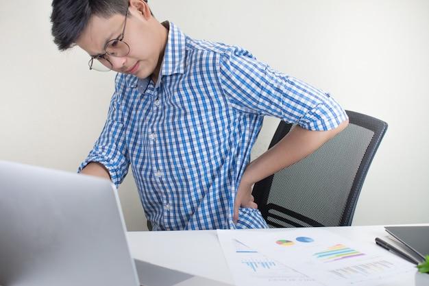 Portret van een aziatische persoon die een plaidoverhemd met rugpijn draagt terwijl het werken op het kantoor. office syndroom. Premium Foto