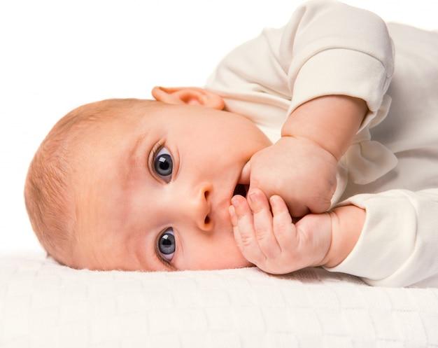 Portret van een baby die in bed thuis ligt. Premium Foto