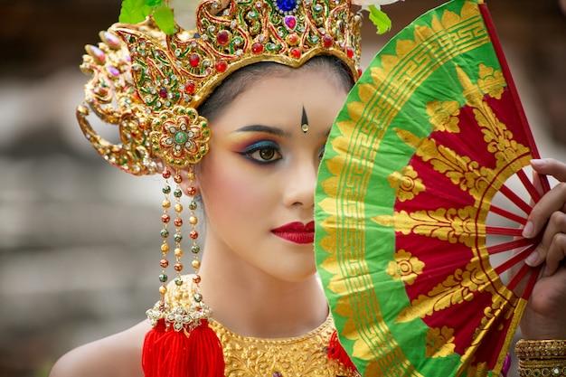 Portret van een balinese dansers houdt vouwen fan Premium Foto