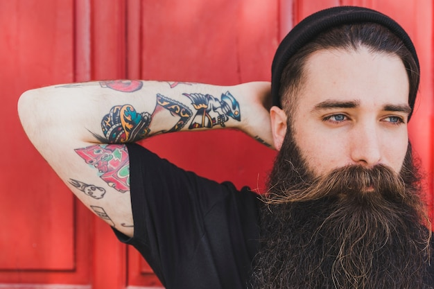 Portret van een bebaarde jonge man met kleurrijke tatoeage op zijn hand tegen rode achtergrond Gratis Foto