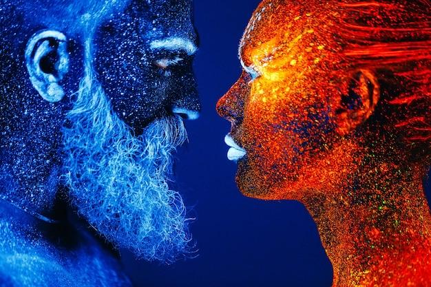Portret van een bebaarde man en vrouw geschilderd in ultraviolet poeder. Premium Foto