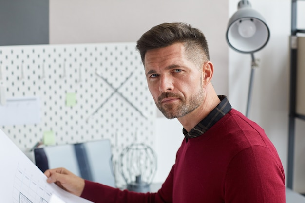 Portret van een bebaarde volwassen man met blauwdrukken en tijdens het werken in de architectuur of bouwsector, Premium Foto