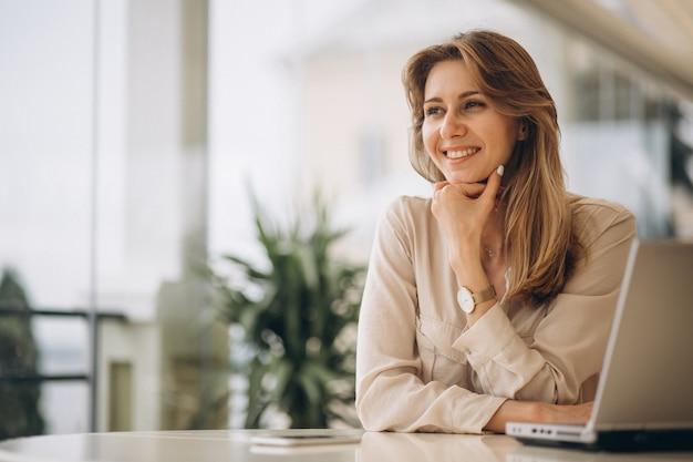 Portret van een bedrijfsvrouw die aan laptop werkt Gratis Foto