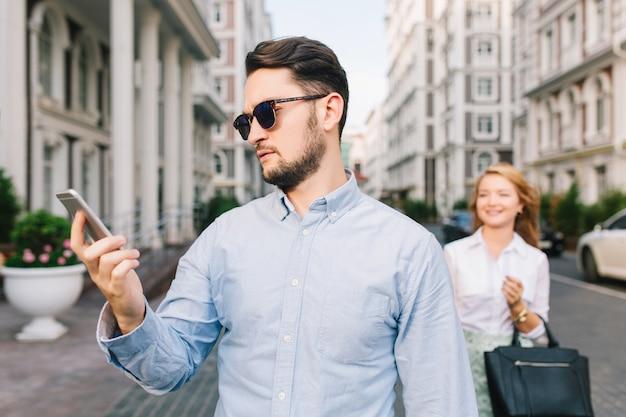 Portret van een beetje triest darm in zonnebril kijken op de telefoon op straat. mooi blond meisje dat hem betrapt Gratis Foto