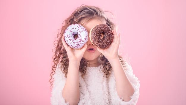 Portret van een beetje verrast meisje met donuts Gratis Foto
